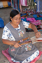 North America, Mexico, Oaxaca Province, Oaxaca, woman using backstrap loop to weave belt