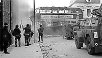 British soldiers shelter behind a hijacked doubledecker bus on the loyalist Shankill Road, Belfast, N Ireland, following an outbreak of violence which was triggered by Protestant supporters of Linfield FC, attacking the predominently Roman Catholic Unity Flats on their way home from a match on Saturday 26th September 1970. The disturbances continued into the third day. 197009260349b<br />