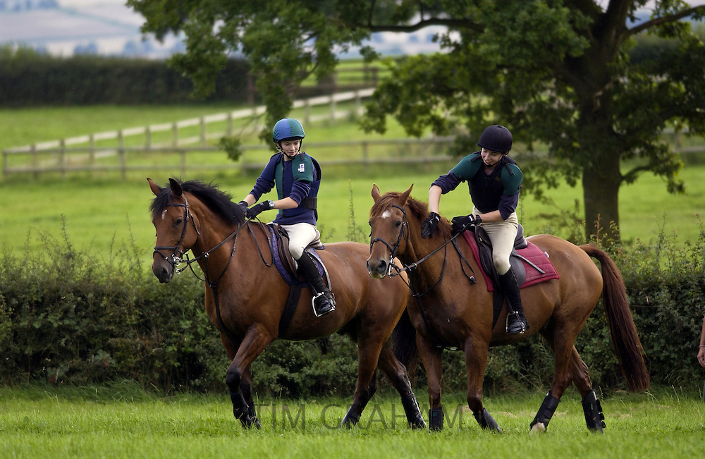 Young riders take their horses for  a slow stroll around a paddock, United Kingdom