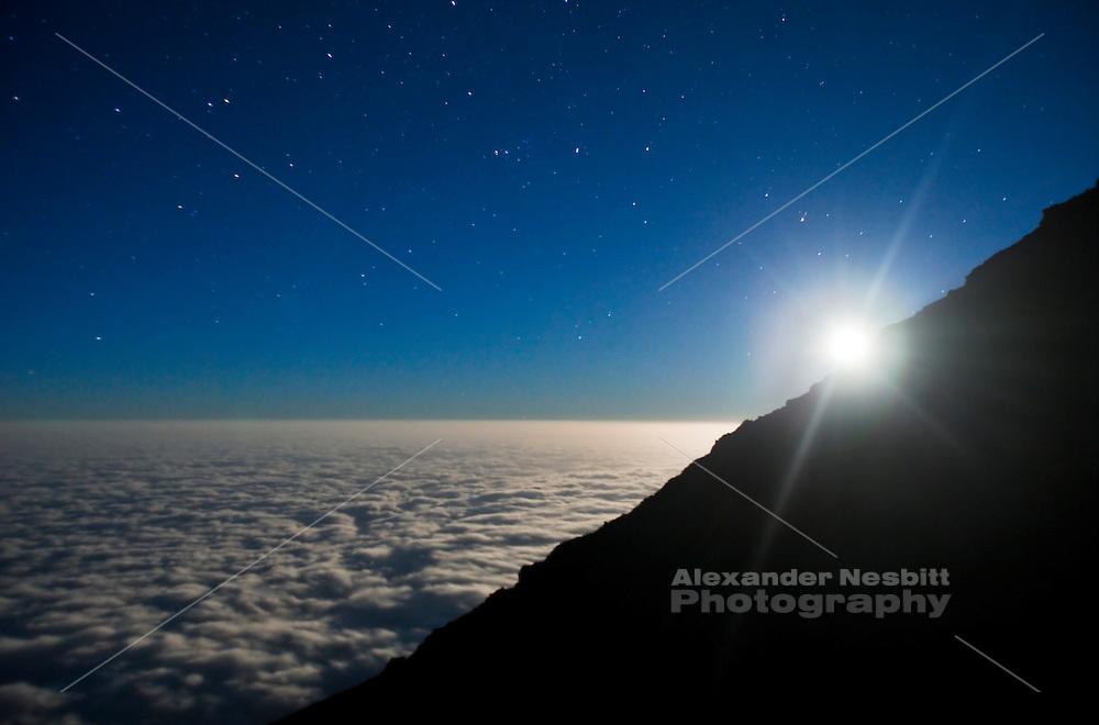 Tanzania - Full moon sets over a roof of clouds. Mt. Kilimanjaro, Tanzania