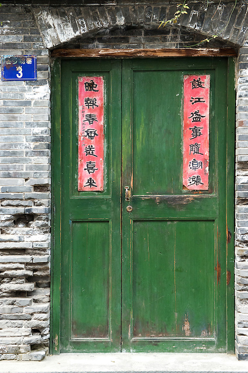 A green wooden door pasted with traditional antithetical couplets written in chinese