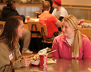 Jamie Erwin (left) talks to U.D. Student Sara Garland, Jr. at a burrito party for the homeless hosted by U.D. Religious Studies student Joe Melendrez at Chipotle's on Brown Street in Dayton.  At the table in the background, Joyce Polite (left) talks to Joe Melendrez (right,) as Pat Tramonte looks on.