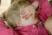 little child hiding behind hand while crying