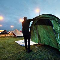 Nederland, Amsterdam , 1 oktober 2014.<br /> De rij caravans met mensen die een zelfbouwkavel willen kopen op het Zeeburgereiland wordt steeds groter.<br /> Sommige staan al een paar weken in de wachtrij totdat ze een kavel mogen kopen. Pas volgende week zaterdag gaan de kavels pas in de verkoop, maar wie weg gaat, verliest zijn plek in de rij.<br /> Een van de kampeerders staat er al een tijdje in zijn caravan: 'Ik ben hier behoorlijk vroeg gaan staan, want er is &eacute;&eacute;n kavel waar ik echt ge&iuml;ntresseerd in ben. Er hoeft er maar een eerder te zijn en dan ben je 'm kwijt.'<br /> De wachtende kopers vinden het best gezellig op het terrein: 'Je ontmoet een soort van je toekomstige buren als het zo doorgaat. Dat geeft een apart campinggevoel en we barbecuen samen.'<br /> Een probleempje, als je weggaat ben je je plek kwijt. 'Als je moet werken moet je zorgen dat er iemand anders op je plek zit. Ik had hier eerst helemaal geen zin in, maar het is toch wel een bizar avontuur.'<br /> Op de foto: Een nieuwkomer slaat zijn tent op.<br /> Foto:Jean-Pierre Jans