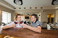 Smiling young couple toasting wine glasses at restaurant counter