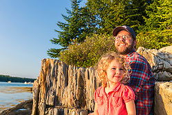 A man and his young daughter sit on a rock ledge on East Gosling Island in Casco Bay, Harpswell, Maine.