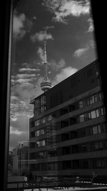 A black and white photograph of the CN Tower, as taken through a window.