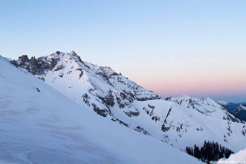 A snow covered mountain summit at dawn light.