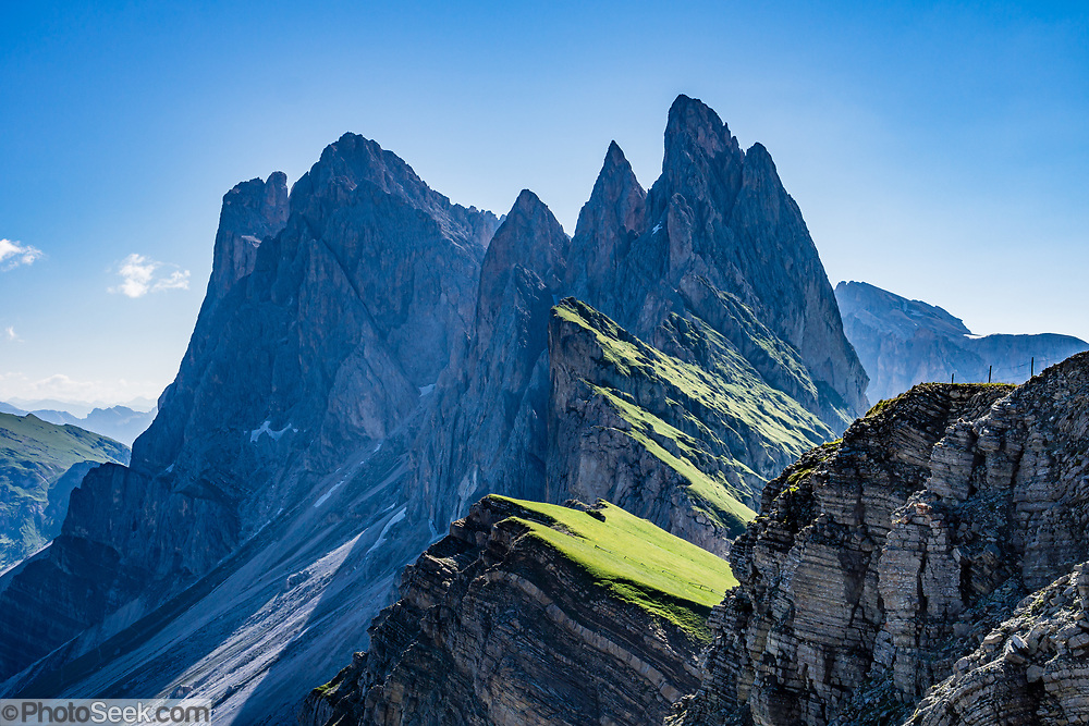 Sharp spires of the Geisler/Odle Group soar above green Alpe di Seceda, above Ortisei, in South Tyrol, the Dolomites, Italy, Europe. The beautiful ski resort of Selva di Val Gardena (German: Wolkenstein in Gröden; Ladin: Sëlva Gherdëine) makes a great hiking base in the Trentino-Alto Adige/Südtirol (South Tyrol) region of Italy. For our favorite hike in the Dolomiti, start from Selva with the first morning bus to Ortisei, take the Seceda lift, admire great views up at the cross on the edge of Val di Funes (Villnöss), then walk 12 miles (2000 feet up, 5000 feet down) via the steep pass Furcela Forces De Sieles (Forcella Forces de Sielles) to beautiful Vallunga (trail #2 to 16), finishing where you started in Selva. The hike traverses the Geisler/Odle and Puez Groups from verdant pastures to alpine wonders, all preserved in a vast Nature Park: Parco Naturale Puez-Odle (German: Naturpark Puez-Geisler; Ladin: Parch Natural Pöz-Odles), including the deeply glaciated U-shaped valley of Vallunga (Langental). As sheep and cows graze en route, Saint Sylvester's Chapel (San Silvestro) in Vallunga is fittingly dedicated to the patron saint of cattle and contains 300-year-old frescoes depicting the life of Jesus. UNESCO honored the Dolomites as a natural World Heritage Site in 2009.