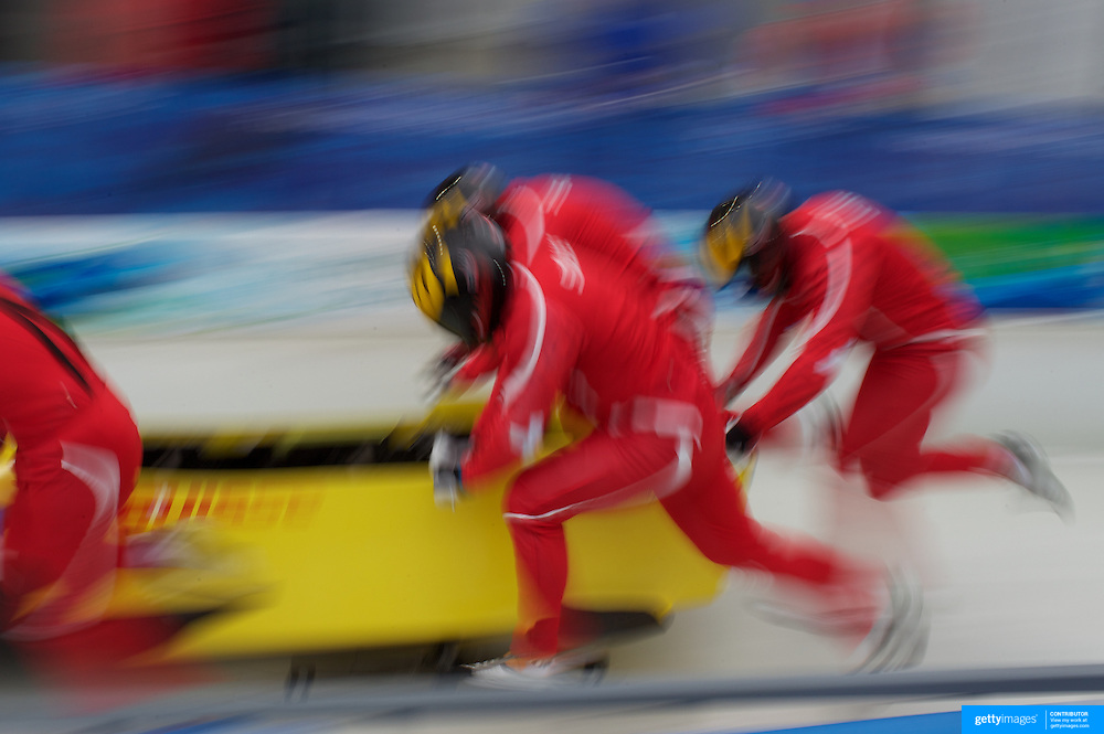 """The Switzeralnd Bobsleigh team at the start during the Bobsleigh Four-man competition  at The Whistler Sliding Centre, Whistler, during the Vancouver Winter Olympics. 25th February 2010. Photo Tim Clayton..'BOB'..Images from the Four-man Bobsleigh Competition. Winter Olympics, Vancouver 2010..History was made at the Whistler Sliding Centre when the USA four-man bobsleigh team, led by Steven Holcomb took the Gold. The first time since 1948, a gap of 62 years, since the USA have won an Olympic Bobsleigh gold and they did it with their sleigh named """"Night Train""""...The four days of practice and competition show the tension, nervousness and preparation as the teams of hardened men cope with the challenge of traveling at average speeds of over 150 km an hour. Indeed, five teams had already pulled out of the event before the opening heats because of track complexity, speed and fear, and on the final day, another four teams did not start after six crashes in the first two heats...Teams warm up behind the start complex, warming muscles in the cold in preparation for the explosive start. Many teams prepare in silence, mentally preparing themselves as they wait at the top of the run, in the bobsleigh sheds and the loading areas for their turn. When it's time to slide each team performs it's own starting ritual, followed by the much practiced start out of the blocks for just over four seconds, the teams are then in the hands of the accomplished drivers as they hurtle down the track for just over fifty seconds...Spectators clamber for the best position on track to see the sleighs for a split second, many unsuccessfully try to capture the moments on camera, The rumble of the sleigh is heard then the crowds gasp as it hurtles past in a blur...The American foursome of  Steven Holcomb, Justin Olsen, Steve Mesler and Curtis Tomasevicz finished with a pooled four-heat time of 3min 24.46sec. The German team led by Andre Lange won the Silver Medal in a combined time of 3min 24.84sec whi"""