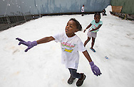 "Children throw snow balls during the annual ""Christmas in July"" event at the Union Rescue Mission in the Skid Row area of Los Angeles, California on Wednesday, July 10, 2013. (Photo by Ringo Chiu/PHOTOFORMULA.com)"