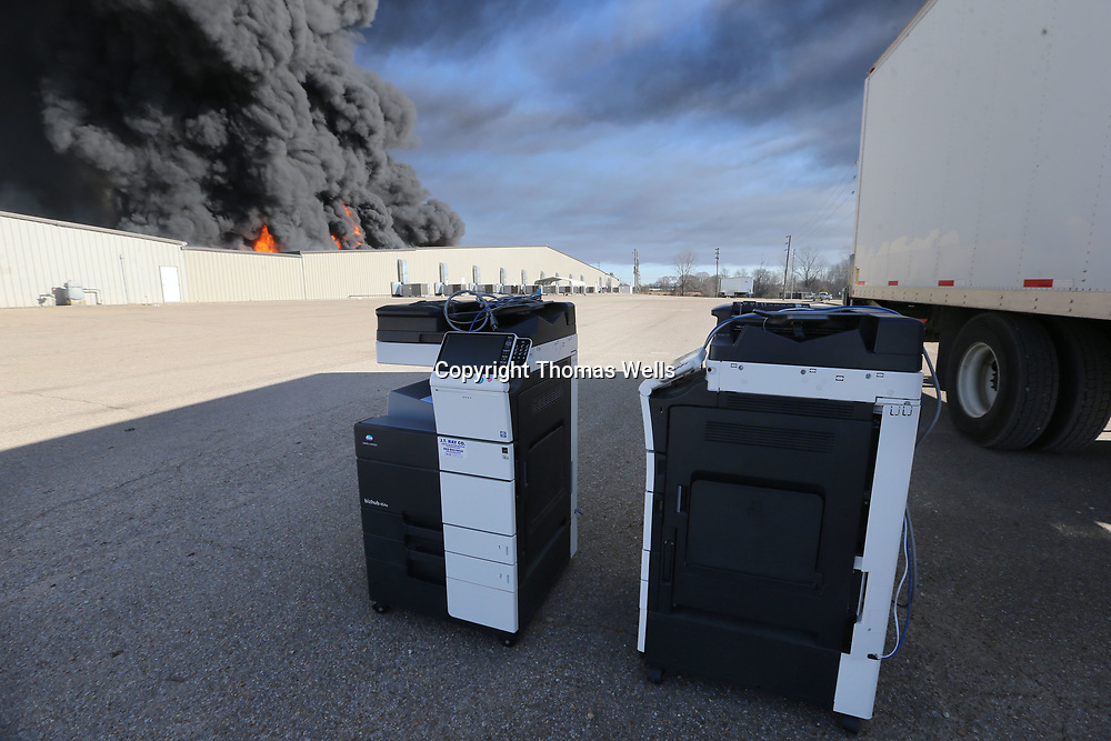Two rescued copy machines stand in the parking lot as the fire races through much of the American Furniture plant on Friday in Ecru.