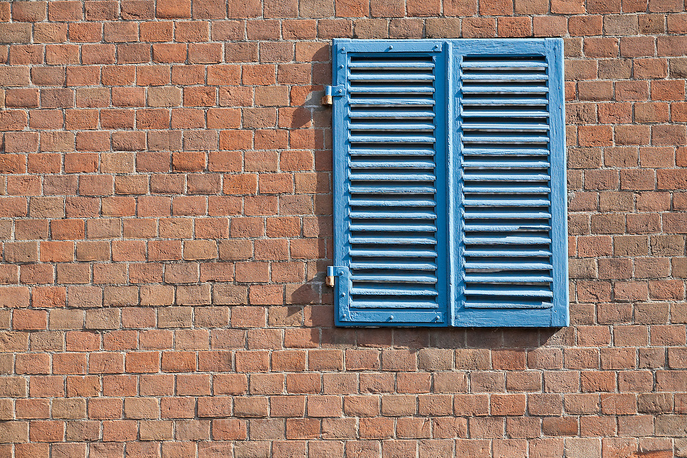 Blue shuttered window contrasts against sun raked brick wall on Prague street