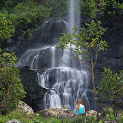 Woman sitting near Tamarin Falls, a little waterfall hike in the interior of Mauritius. You can spend the whole day exploring the seven different layers of the waterfall. A guide is recommended.