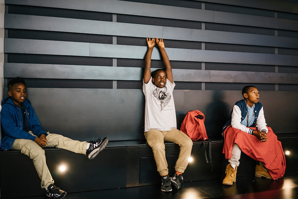 Sixth-graders from Knowledge Is Power Program (KIPP) DC, including Tyron Proctor, 11, left, Omari Sterling, 11, right, and Tay'sean Barrow, 12, watch a video about African American athletes inside the Smithsonian National Musuem of African American History and Culture during their visit on Oct 21, 2016. The students spent an hour touring the new Washington, D.C. museum, which is only available to see with reserved tickets during the first year.