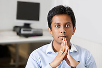 Portrait of young pensive businessman with hands clasped sitting at office