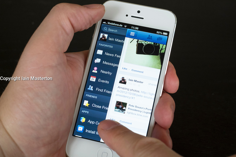 Close-up detail of man holding new iPhone 5 smart phone showing Facebook app and Timeline for user