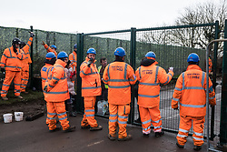 Harefield, UK. 8 February, 2020. HS2 Servest engineers try to prevent environmental activists from Save the Colne Valley, Stop HS2 and Extinction Rebellion from accessing an area of Harvil Road fenced off in order to carry out tree felling works for the high-speed rail project. The activists were successful in preventing any of the scheduled tree felling by HS2 and after an intervention by a police officer all tree felling work has now been cancelled for the weekend.