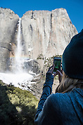 A girl takes a phone picture of Upper Yosemite Falls, Yosemite National Park, California.