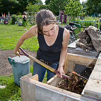 A young, healthy woman turning a compost pile in a community garden.