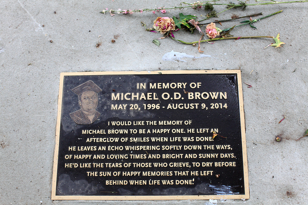 The Michael Brown Jr. memorial plaque, located on Canfield Dr., is adorned with flowers as demonstrators pay their respects on the one year anniversary of his death.