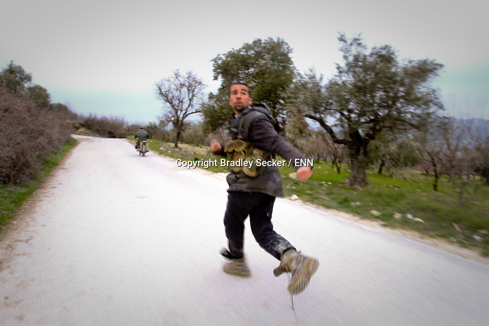 A Free Syrian Army soldier runs for cover as government forces fire shots towards the town of Al Janoudiyah, Syria.
