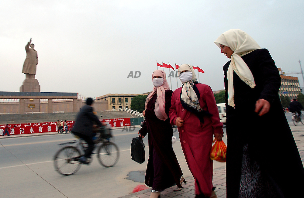 Muslim women walk near Mao Tze Dong statue in People's square.