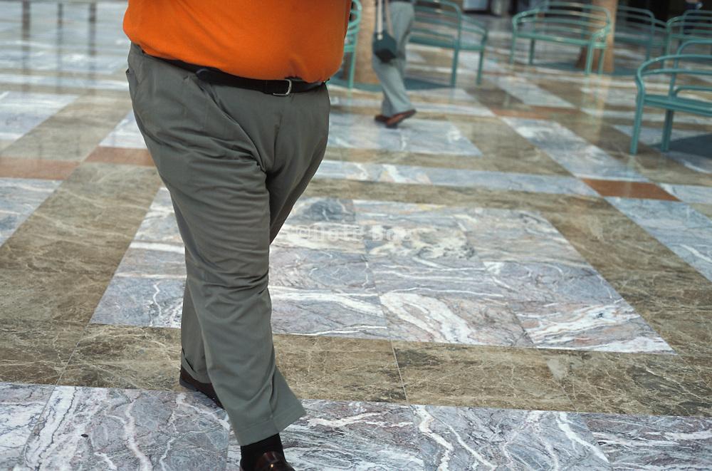 Lower half of an obese man in an orange shirt walking