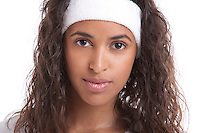 Portrait of young woman with headband against white background