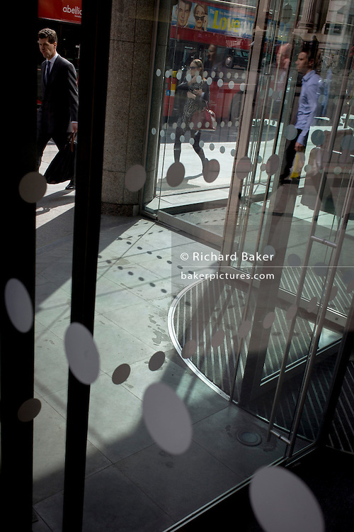 Workers pass an office foyer entrance featuring dots and circles (and shadows) on exterior windows in the City of London.