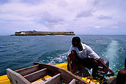 Fisherman leaves behind Saint Sebastian Fortress in Ilha de Mozambique / On the left side is seen Our Lady of the Bastion Church, the oldest european builiding in South Hemisphere