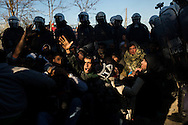 """No fight,"" a man shouts to a group of Greek riot police, equipped with tear gas, surrounding a group of asylum seekers who had barricaded the Greek border crossing to Macedonia near Idomeni on December 3, 2015 in protest of Macedonia's border restrictions. On November 17, 2015 Macedonia, Serbia, Slovenia and Croatia enacted border restrictions which blocked all asylum seekers, except those with documents proving they were from Syria, Iraq and Afhanistan, from entering any of those countries. According to UNHCR, over 60,000 asylum seekers are currently stranded in Greece due to these restrictions."
