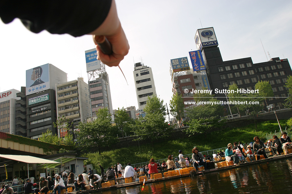During the 'Golden Week' holidays Tokyo people take to Ichigaya Fishing Centre, located in the outer moat of the Imperial Palace. To sit, catching carp, in the fish tanks costs approximately 3 GBP per hour, with rods and bait costing a little extra. Tokyo, Japan, 05.05.06