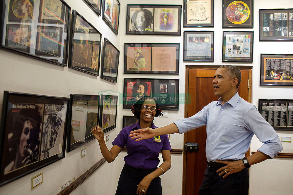 President Barack Obama looks at memorabilia with museum guide Natasha Clark at the Bob Marley Museum in Kingston, Jamaica, April 8, 2015. (Official White House Photo by Pete Souza)<br /> <br /> This official White House photograph is being made available only for publication by news organizations and/or for personal use printing by the subject(s) of the photograph. The photograph may not be manipulated in any way and may not be used in commercial or political materials, advertisements, emails, products, promotions that in any way suggests approval or endorsement of the President, the First Family, or the White House.
