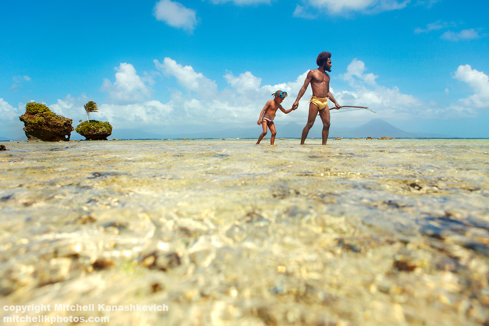 The men of Rah Lava have fished with a bow and arrow in the crystal clear waters around the island for countless generations. A father and son walk through the shallow waters of the reef at low tide. Rah Lava Island, Torba Province, Vanuatu