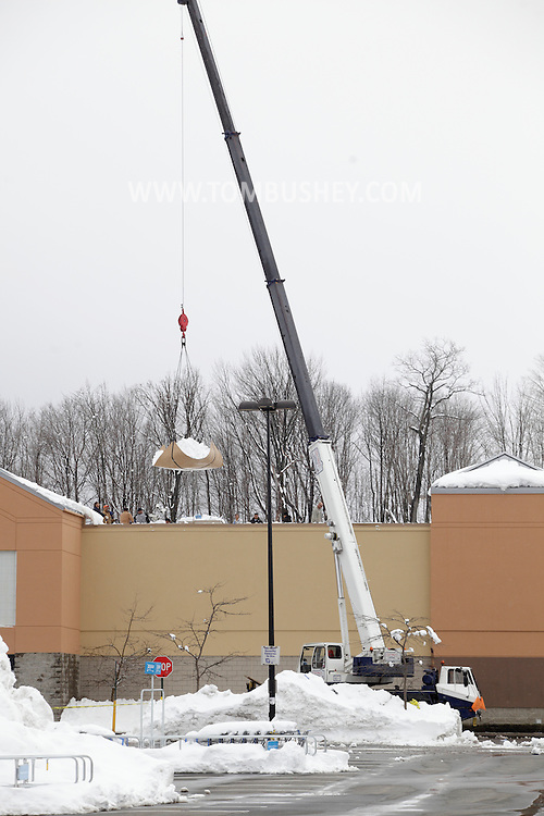 Harriman, New York - A crane lifts a tarp full of snow off the roof of the Walmart store after than 30 inches of snow fell after a storm on Feb. 27, 2010. The store remained closed until the snow was removed and the roof was inspected.