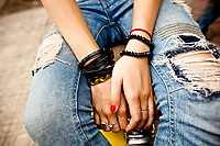Torn jeans and bracelets on a young Vietnamese teenager in Hanoi, Vietnam.