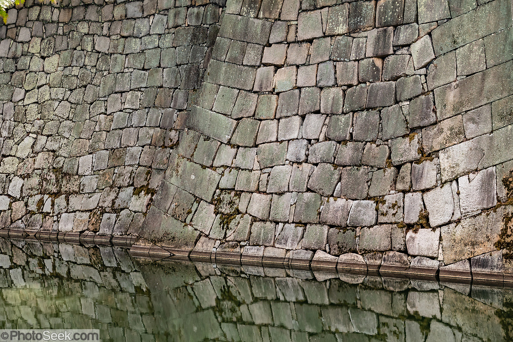 A wall reflects in the moat around Nijo Castle (Nijo-jo) in Kyoto, Japan. Nijo Castle (Nijo-jo) was built in 1603 as the Kyoto residence of Tokugawa Ieyasu, the first shogun of the Edo Period (1603-1867). His grandson Iemitsu completed the castle's palace buildings 23 years later and further expanded the castle by adding a five-story castle keep. After the Tokugawa Shogunate fell in 1867, Nijo Castle was used as an imperial palace for a while before being donated to the city and opened to the public as a historic site. Its palace buildings are some of the best surviving examples of castle palace architecture of Japan's feudal era, and the castle was designated a UNESCO world heritage site in 1994.