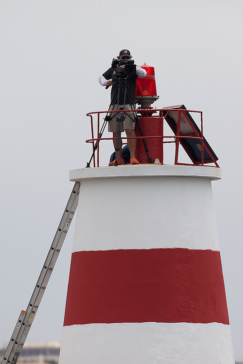 Camerman Digby Fox up on the lighthouse at the to Portimao Harbour. Portimao Portugal Match Cup 2010. World Match Racing Tour. Portimao, Portugal. 25 June 2010. Photo: Gareth Cooke/Subzero Images
