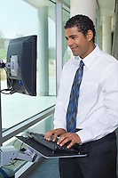 Business man using internet on computer in office hallway