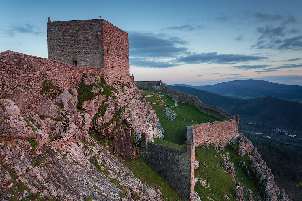 The warm light of sunset bathes the castle walls and its main tower in a reddish hue. The town's name, Marvão, is derived from an 8th-century Muslim duke, named Ibn Marwan who used the fortress as a power base when establishing an independent statelet during the moorish occupation of Portugal.