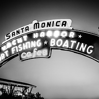 "Santa Monica Pier sign black and white photo.  The famous Santa Monica Pier sign says ""Santa Monica Yacht Harbor Sport Fishing Boating Cafes"". Santa Monica Pier is a landmark located in Los Angeles County Southern California."