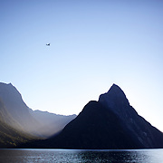 A plane flies over Mitre Peak at sunset. Mitre Peak is an iconic mountain in the South Island of New Zealand. It is one of the most photographed peaks in the country. Part of the reason for its iconic status is its location. Close to the shore of Milford Sound, in the Fiordland National Park in the southwestern South Island, it is a stunning sight. Rising to 1,692 metres from the water of the sound. it is actually a closely grouped set of five peaks, although from most easily accessible viewpoints it appears as a single point. Milford Sound,  Milford Sound, New Zealand. 29th April 2011. Photo Tim Clayton