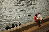 A couple enjoys a Sunday afternoon along the Seine River, Paris, France