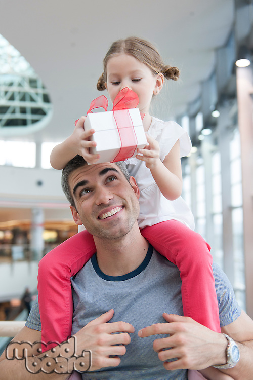 Young daughter sits on fathers shoulders and gives him a present
