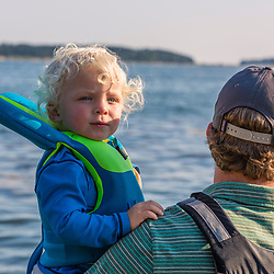 A man carries his young son ashore on East Gosling Island in Casco Bay, Harpswell, Maine.