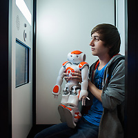 Lyon, France - 19 March 2014: a young man poses for a picture with robot NAO by Aldebaran at Innorobo 2014, the 4th international trade show on service robotics.