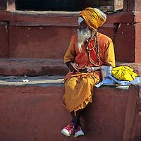 Asia, Nepal, Bhaktapur. A Sadhu in sneakers sits in Durban Square, Bhaktapur.