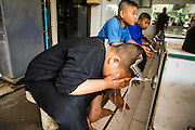 """11 JANUARY 2013 - BANGKOK, THAILAND:   Muslim boys perform ablutions (ritual cleansing required before prayers) before noon prayers in a mosque in the Ban Krua neighborhood in Bangkok. The Ban Krua neighborhood of Bangkok is the oldest Muslim community in Bangkok. Ban Krua was originally settled by Cham Muslims from Cambodia and Vietnam who fought on the side of the Thai King Rama I. They were given a royal grant of land east of what was then the Thai capitol at the end of the 18th century in return for their military service. The Cham Muslims were originally weavers and what is known as """"Thai Silk"""" was developed by the people in Ban Krua. Several families in the neighborhood still weave in their homes.            PHOTO BY JACK KURTZ"""