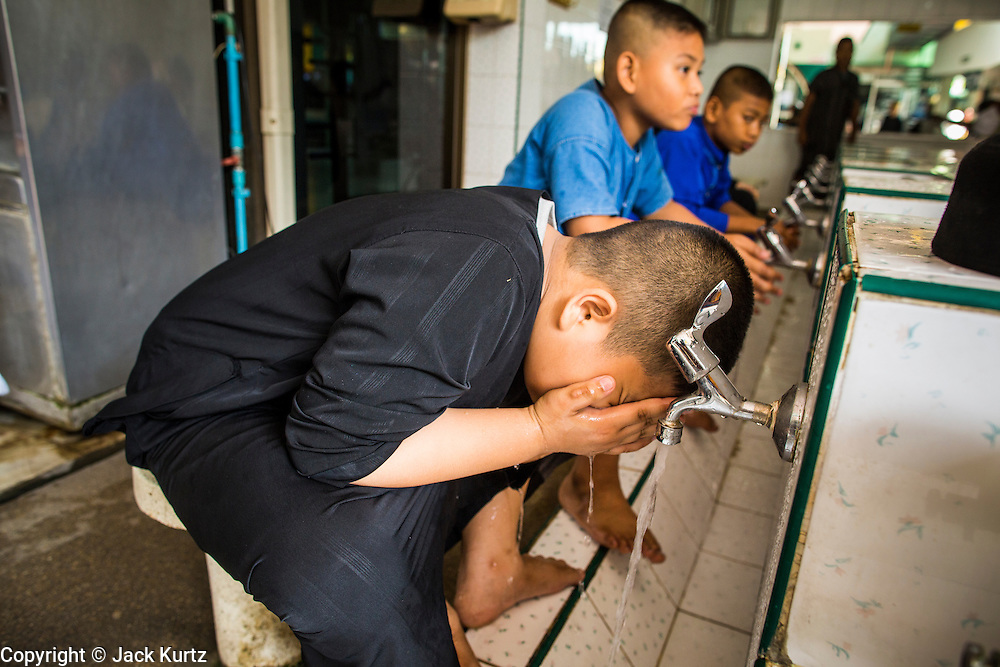 "11 JANUARY 2013 - BANGKOK, THAILAND:   Muslim boys perform ablutions (ritual cleansing required before prayers) before noon prayers in a mosque in the Ban Krua neighborhood in Bangkok. The Ban Krua neighborhood of Bangkok is the oldest Muslim community in Bangkok. Ban Krua was originally settled by Cham Muslims from Cambodia and Vietnam who fought on the side of the Thai King Rama I. They were given a royal grant of land east of what was then the Thai capitol at the end of the 18th century in return for their military service. The Cham Muslims were originally weavers and what is known as ""Thai Silk"" was developed by the people in Ban Krua. Several families in the neighborhood still weave in their homes.            PHOTO BY JACK KURTZ"